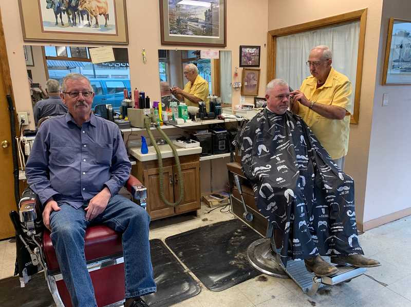 PMG PHOTO: CAROL ROSEN - Bill Caster waits patiently for his turn for a haircut from 80-years young Harold Hall at the barber shop Hall opened 50 years ago.