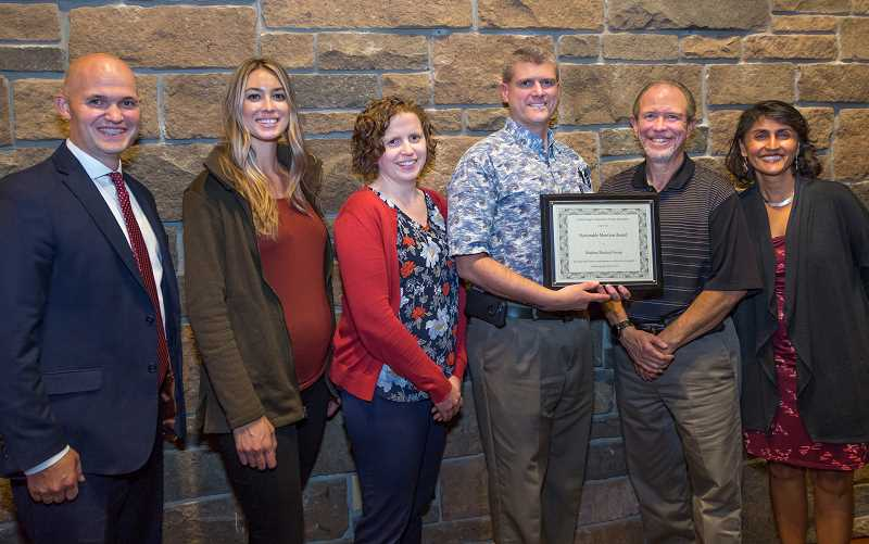 SUBMITTED PHOTO - At left, Kim Bangerter, the CEO of Central Oregon Independent Practice Association, awards Madras Medical Group with an honorable mention award for 2019 primary care at the group's recent annual meeting. Accepting the award were, from left to right, Physician's Assistant Molly Nichols, Dr. Joanne Boisvert, Dr. Gary Plant, and Bob Jones, administrator of Madras Medical Group. At right is Dr. Divya Sharma, chief medical officer of COIPA.