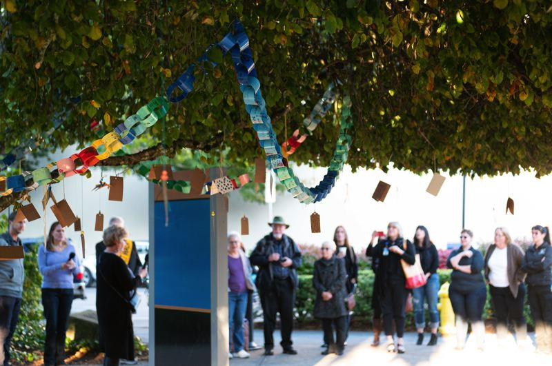PMG PHOTO: CHRIS OERTELL - Colorful wishing chains made by students at Lincoln Street Elementary School and Glencoe High School hang on a weeping elm tree during the opening ceremony for Hillsboro's wishing tree at the Washington County Courthouse in Hillsboro, Ore., on Tuesday, Oct. 1, 2019.