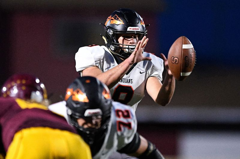 PMG PHOTO: CHRISTOPHER OERTELL - Quarterback Jakobi Kessi of Scappoose High takes a snap from center.