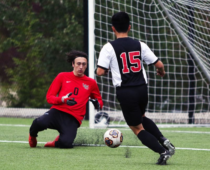 PMG PHOTO: DAN BROOD - Westside Christian senior goalkeeper Sean Thomas (left) slides to grab the ball during the Eagles' match with Portland Adventist Academy on Oct. 2.