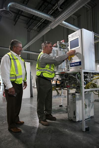 PAMPLIN MEDIA GROUP: JAIME VALDEZ - Mark Prusiecki (right) general manager, Hillsboro Product Company, Edwards Vacuum LLC, and Scott Balaguer, vice president and general manager of Edwards Semiconductor division North America, with an exhaust system at Edwards' new American headquarters at 6220 N.E. Century Boulevard, Hillsboro. As well as offices, sales and training, the building receives parts from around the world which are then assembled and shipped off to big chipmakers.