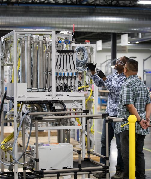 PAMPLIN MEDIA GROUP: JAIME VALDEZ - Assembly workers at Edwards in Hillsboro put together an integrated system. The machines provide vacuums and remove gasses and liquids from the kind of high-tech tools used in making microchips.