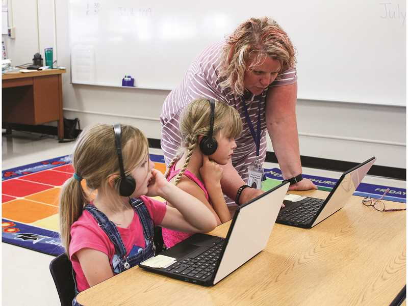 PHOTO COURTESY OF CROOK COUNTY SCHOOL DISTRICT  - Kiwanis Summer School teacher Stacy Stringer assists Eva Petersen while Quincy McCullough, left, works on a lesson.