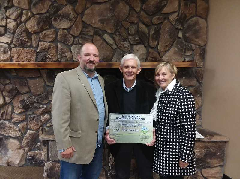COURTESY PHOTO: CATHY RAE SMITH - Marty Nash (center) accepts the 2019 Business Beautification Award on behalf of Pioneer Chapel at the chamber luncheon Oct. 1. Chamber Director Kyle Lang (left) and Canby Area Beautification President Cathy Rae Smith present the award.