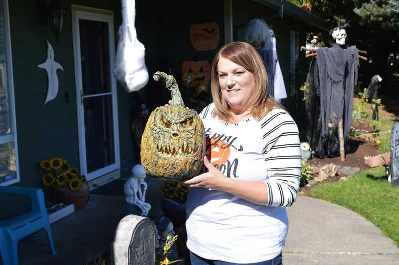 PMG PHOTO: DARRYL SWAN - Kristen Younts holds a jack-o-lantern she made as part of a display at the Scappoose Halloween House located on SW 4th Street in Scappoose. The foam jack-o-lantern was detailed using decoupage paint and paper towels.