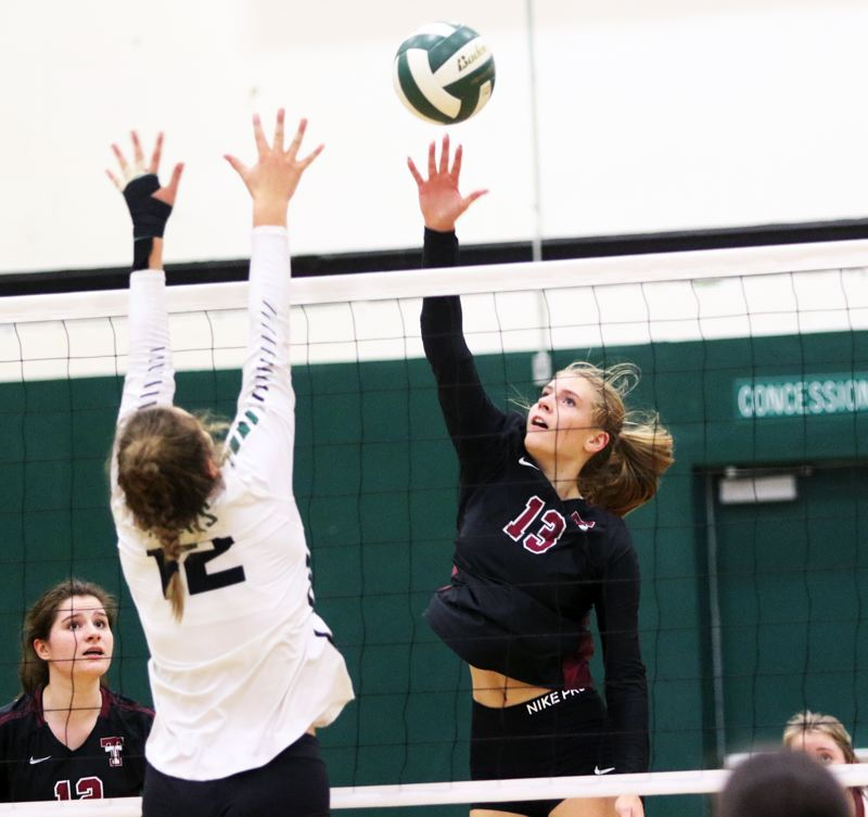 PMG PHOTO: DAN BROOD - Tualatin HIgh School junior Kylie Zralka (right) looks to hit the ball past Tigard sophomore Anna Follett during Thursday's match. The Wolves won 3-0.