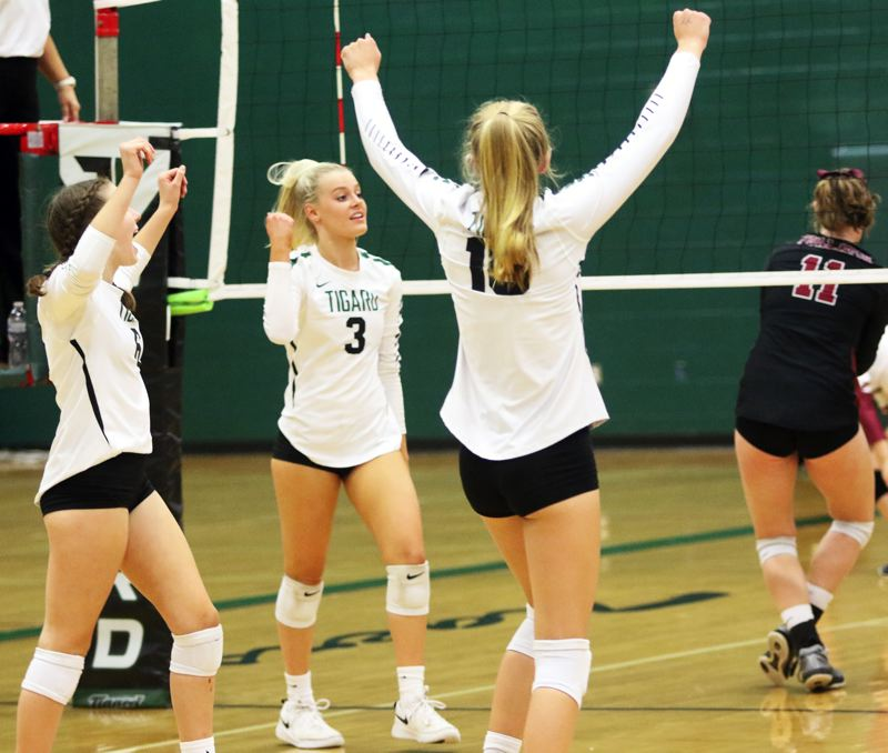PMG PHOTO: DAN BROOD - Tigard players Erin Bullard (3) and Kaitlynn Peterson celebrate a point during the Tigers' Three Rivers League match at Tualatin on Thursday.