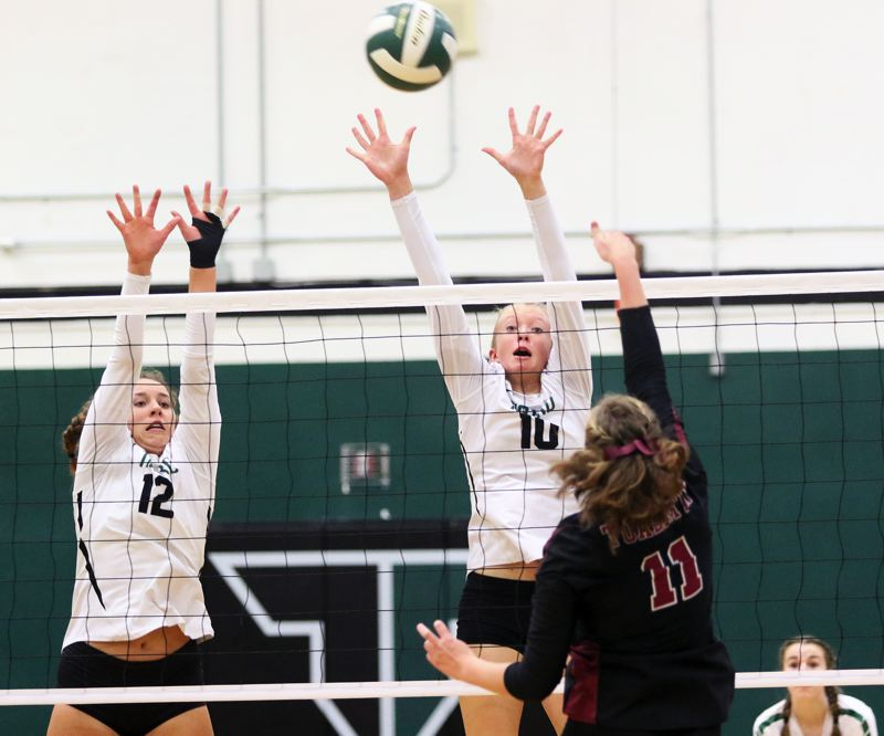 PMG PHOTO: DAN BROOD - Tigard sophomores Anna Follett (12) and Kaitlynn Peterson go up for a block during the Tigers' Three Rivers League match at Tualatin.
