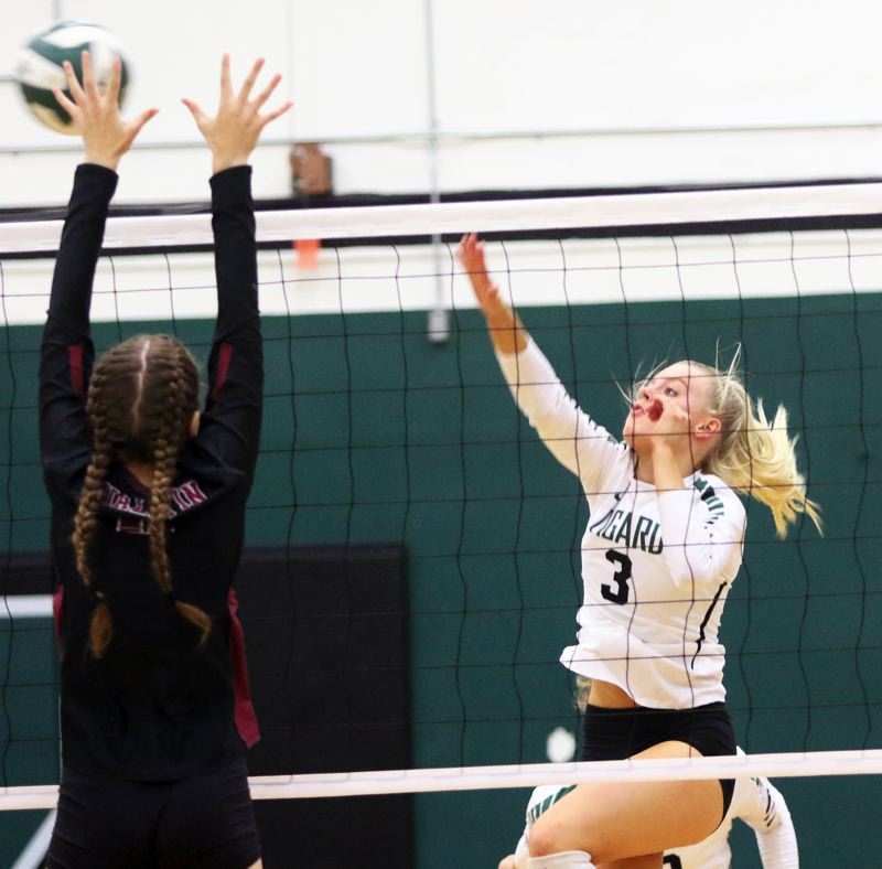PMG PHOTO: DAN BROOD - Tigard High School sophomore Kaitlynn Peterson (right) hits the ball over the net during the Tigers' match at Tualatin on Thursday.