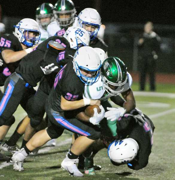 GRAPHIC PHOTO: GARY ALLEN - The Newberg defense swarms a Reynolds running back Friday in the Tigers' nonconference win against the Raiders.