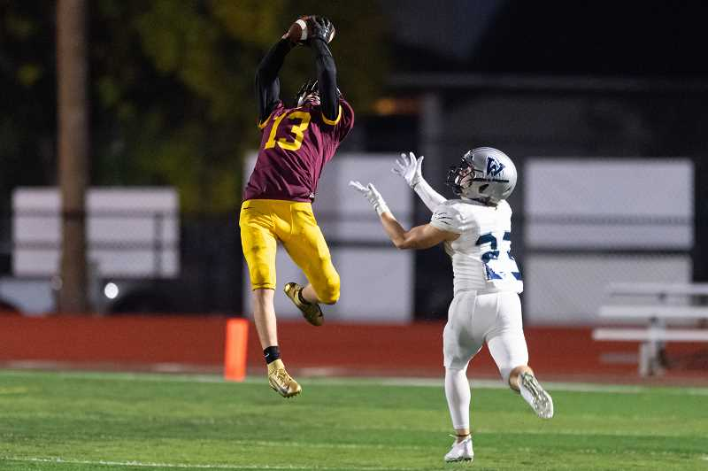 PMG PHOTO: CHRISTOPHER OERTELL - Forest Grove's Cameron Ulloa goes up to make a leaping interception over Wilsonville's Payton Dart during the Vikings' game against the Wildcats Friday, Oct. 4, at Forest Grove High School.