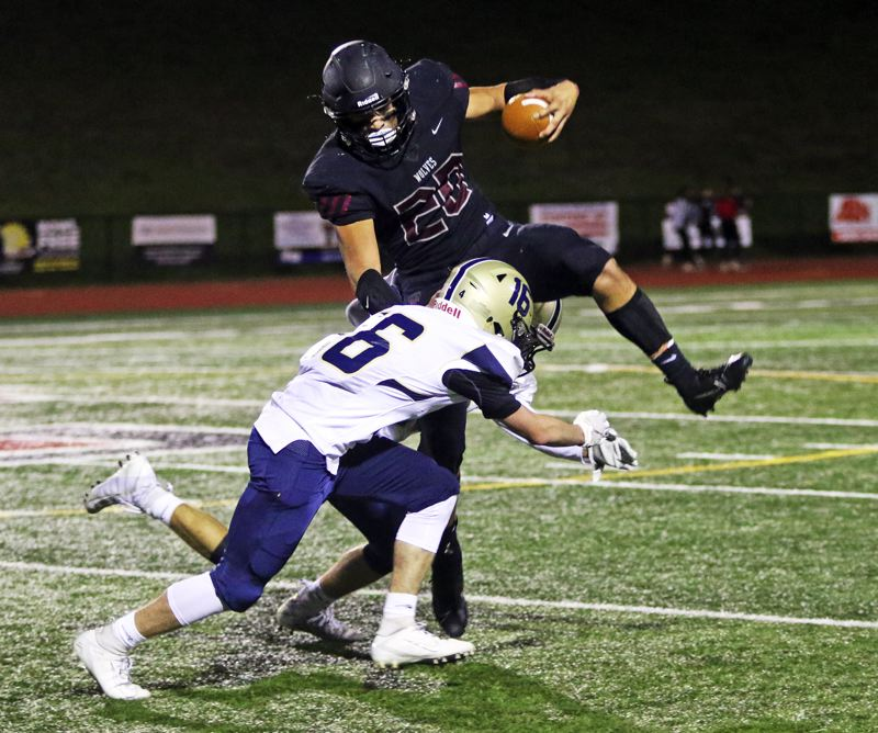 PMG PHOTO: DAN BROOD - Tualatin High School senoir John Miller (20) gets ready to try and leap over Canby junior Jackson Valdrow. Miller had two touchdown catches in the Wolves' 62-33 victory.