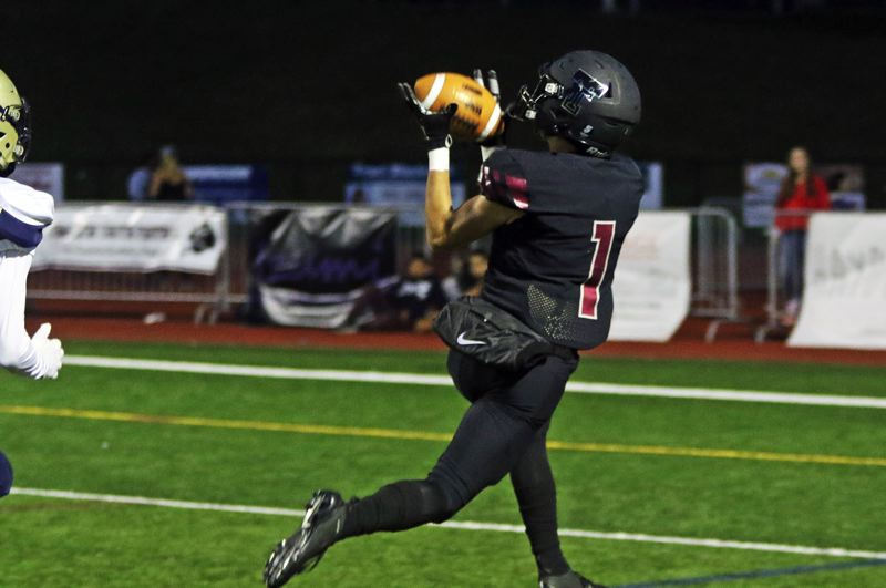 PMG PHOTO: DAN BROOD - Tualatin High School senior receiver Cade McCarty catches the football on his way to scoring the first of his two touchdowns in the 62-33 win over Canby.