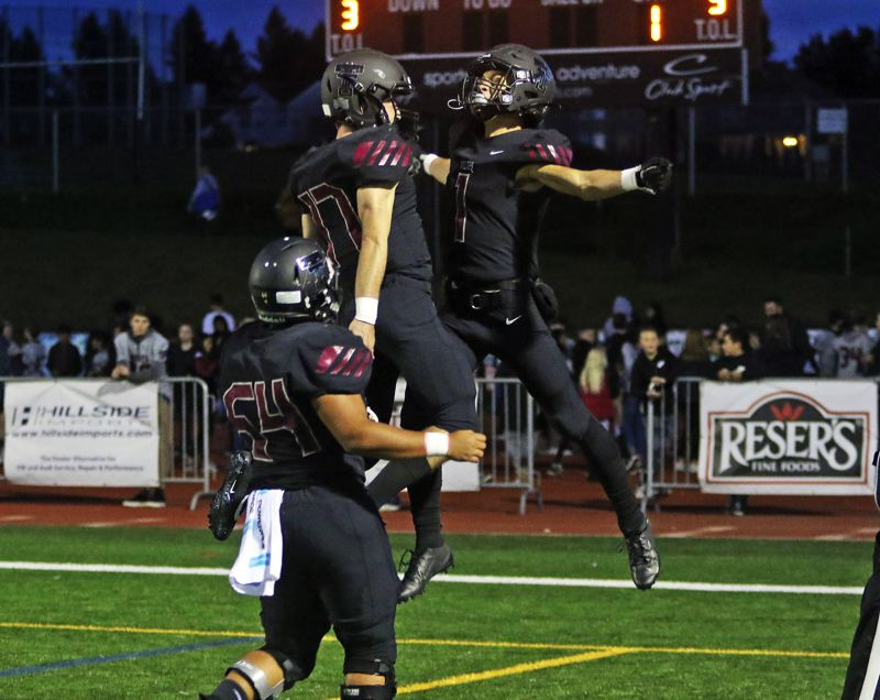 PMG PHOTO: DAN BROOD - Tualatin players catch some air to celebrate a score during their team's 62-33 win over Canby on Friday, Oct. 4, at Tualatin High School.
