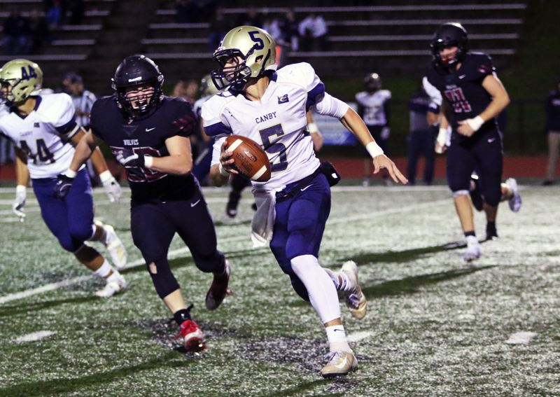 PMG PHOTO: DAN BROOD - Canby High School sophomore quarterback Michael Gibson looks for running room during Friday's game at Tualatin. Gibson threw four touchdown passes in the contest.