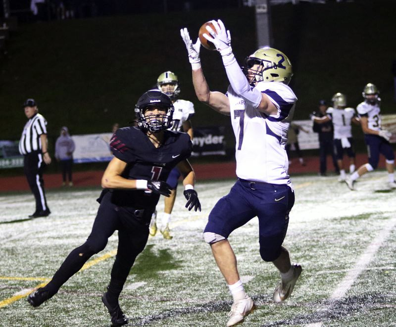 PMG PHOTO: DAN BROOD - Canby High School senior receiver Jackson Linman (right) grabs the football on his way to scoring the first of his two touchdowns during Friday's game at Tualatin.