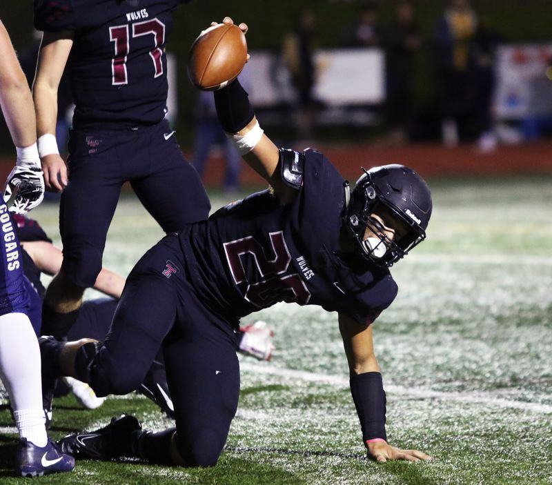 PMG PHOTO: DAN BROOD - Tualatin High School senior John Miller holds up the football after recovering a Canby football near the goal line during Friday's Three Rivers League game.