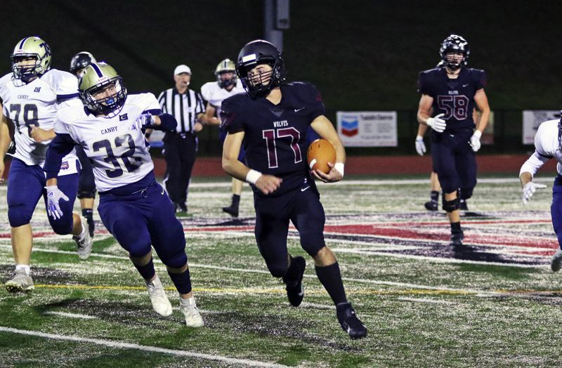 PMG PHOTO: DAN BROOD - Tualatin High School senior quarterback Blake Jackson (17) scrambles for yardage during the Wolves' 62-33 win over Canby on Friday.