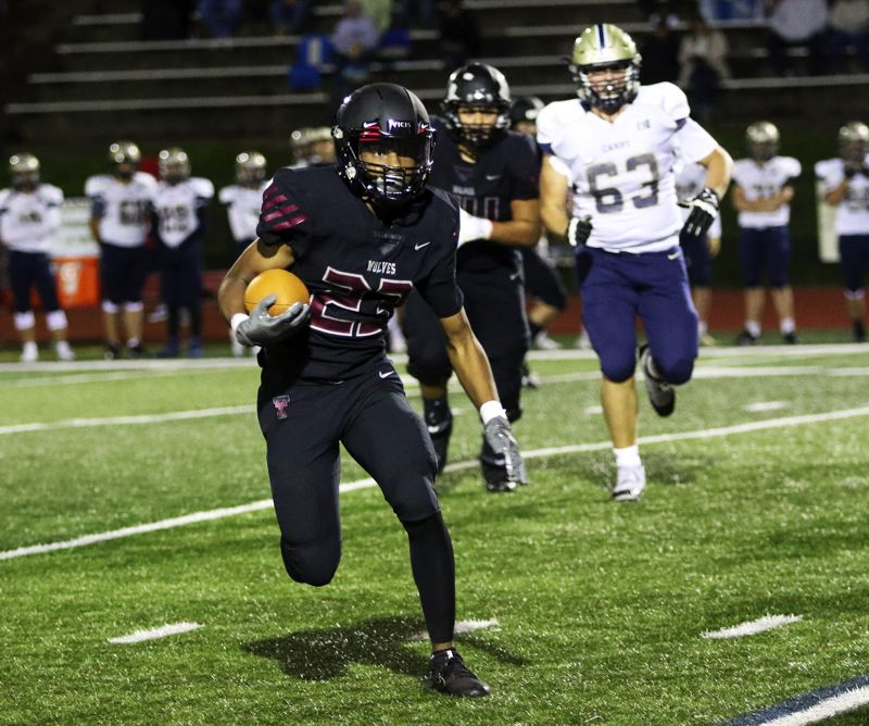 PMG PHOTO: DAN BROOD - Tualatin High School sophomore Malik Ross turns the corner on his way to scoring on a 32-yard run during the Wolves' 62-33 league win over Canby on Friday.