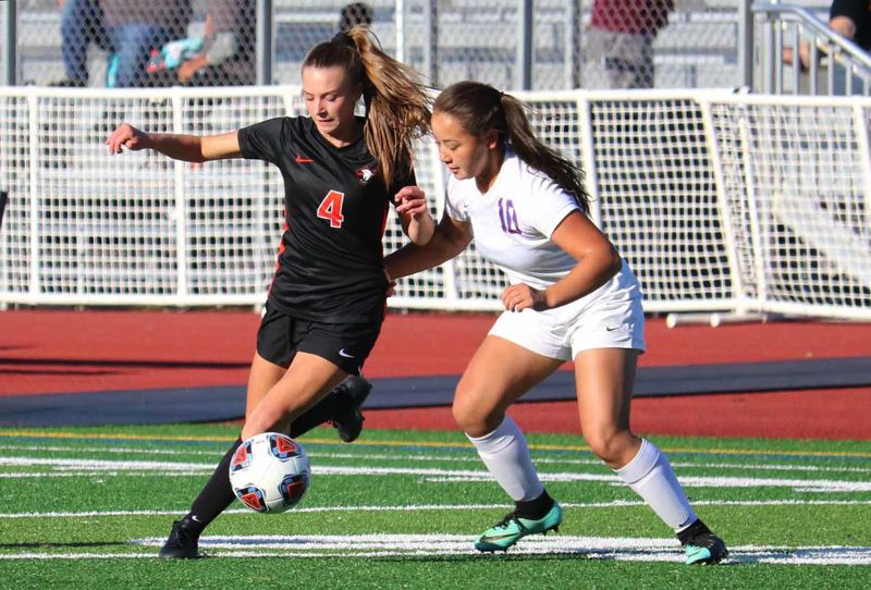 PMG PHOTO: JIM BESEDA - Gladstone's Brianna Lewis (4) wheels around Madras defender Harlee David (10) during the first half of Tuesday's Tri-Valley Conference girls soccer game at Gladstone. The Gladiators won 7-0.