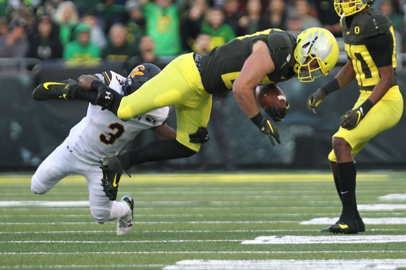 PMG PHOTO: JAIME VALDEZ - Oregon tight end Jacob Breeland goes flying with a catch Saturday against California at Autzen Stadium.