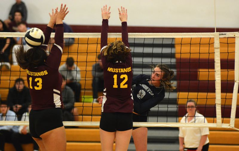 PMG PHOTO: DEREK WILEY - Wilsonville sophomore Ashli Edmiston hits the ball past a pair of Milwaukie blockers Tuesday.