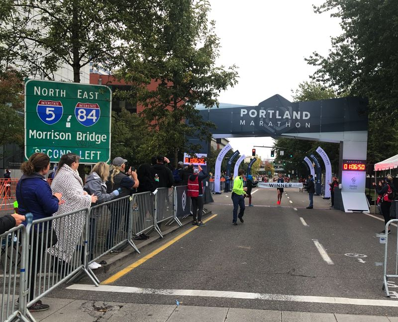 PMG PHOTO: STEVE BRANDON - Mark Messmer hits the tape as winner of the half-marathon in downtown Portland on Sunday.