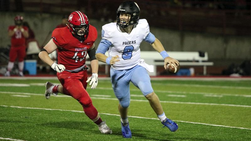 PMG PHOTO: JIM BESEDA - Lakeridge quarterback Cooper Justice eludes Oregon City defensive end Hayden Miller during the third quarter of his team's 37-10 win at Oregon City on Friday, Oct. 4.
