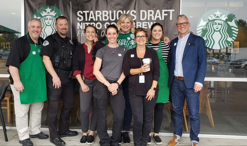 COURTESY PHOTO - Milwaukie Police Capt. Ryan Burdick (from left), Officer Greg Elkins, Detective Kathryn Meier, Evidence Tech Michelle Verhaeghe, Milwaukie Marketplace store manager Jenny Hollingsworth, Records Specialist Tanya Anderson, Starbucks Shift Supervisor Alexis Watkins and Starbucks District Manager Casey Walsh.