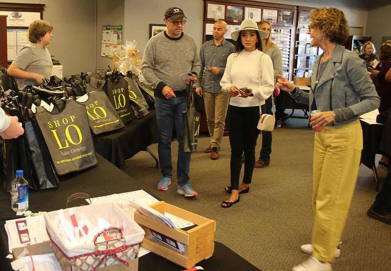 PMG PHOTO: J. BRIAN MONIHAN  - Penelope Fain helps one of the 500 attendees check in at the Lake Oswego Chamber of Commerce office, the start of the LO Wine Walk. Fain, from Freeman Motor Company, was one of the event organizers.