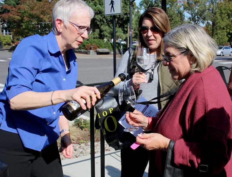 PMG PHOTO: J. BRIAN MONIHAN - LO Wine Walk attendees had the opportunity to sample up to 12 different wines, one per business, like this stop at Duke's Public House on A Avenue. With 28 downtown businesses on the tour, attendees did have to choose wisely.