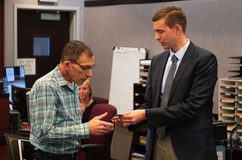 PMG PHOTO: CHRIS OERTELL - District attorney Kevin Barton presents Frank Damato with a challenge coin during a graduation day ceremony for the Veterans Treatment Court at Washington County Courthouse in Hillsboro, Ore., on Thursday, Oct. 3, 2019.