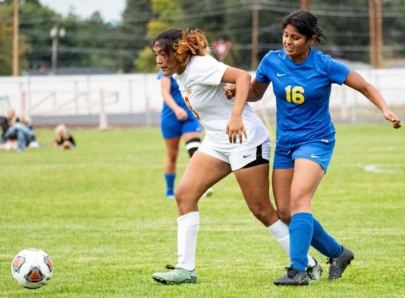 LON AUSTIN/CENTRAL OREGONIAN - Isabel Vargas Martinez, far right, fights with a The Dalles player for a ball during a match earlier this year. Vargas Martinez made a stop in the goal against Pendleton on Thursday but the Cowgirls lost 4-0.