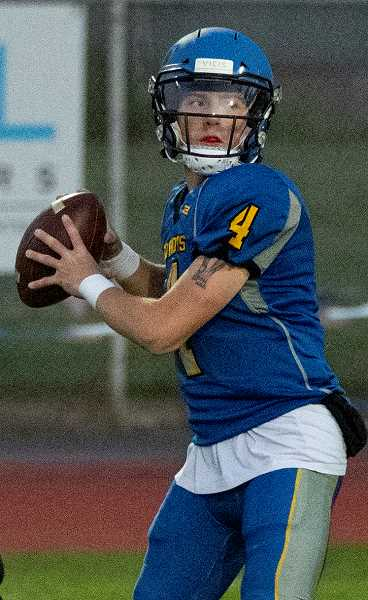 LON AUSTIN/CENTRAL OREGONIAN - Brody Connell drops back to pass in a game earlier this year. Connell went 14-20 with a touchdown in the Cowboys' 17-14 overtime loss to North Marion last Friday.
