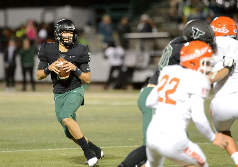 COURTESY PHOTO: CHRIS GERMANO - Tigard High School junior quarterback Drew Carter (left) drops back to pass during the Tigers' 56-0 win over Sprague. Carter completed all four of his passes for 82 yards and three TDs.