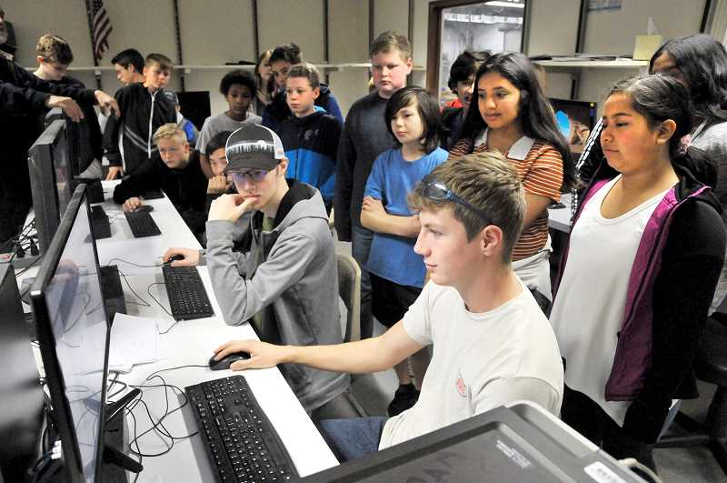 GRAPHIC PHOTO: GARY ALLEN - NHS senior Brogan Sattler demonstrates a CAD program for a group of middle school students during the open house Friday at the high school.