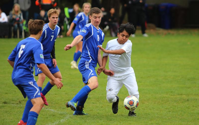 PMG PHOTO: JIM BESEDA - North Clackamas Christian's Braden Young (8, blue) challenges Grand View Christian Academy's Andrew Park during the first half of Tuesday's 1A Special District 7 soccer match in Oregon City.