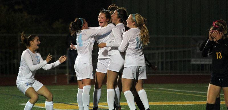 PMG PHOTO: MILES VANCE - Lakeridge senior Megan McCormack (center) gets congratulated by teammates after scoring the lone goal in her team's 1-0 win over West Linn at West Linn High School on Tuesday, Oct. 8.
