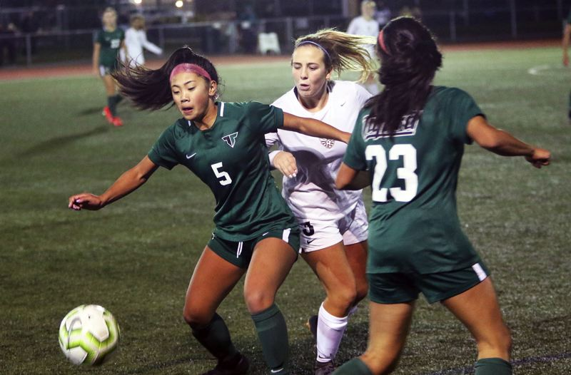 PMG PHOTO: DAN BROOD - Tigard High School freshman Jaiden Riodil (5) battles for the ball in front of Tualatin senior Darci Chamberlin during the teams' Three Rivers League match on Tuesday.