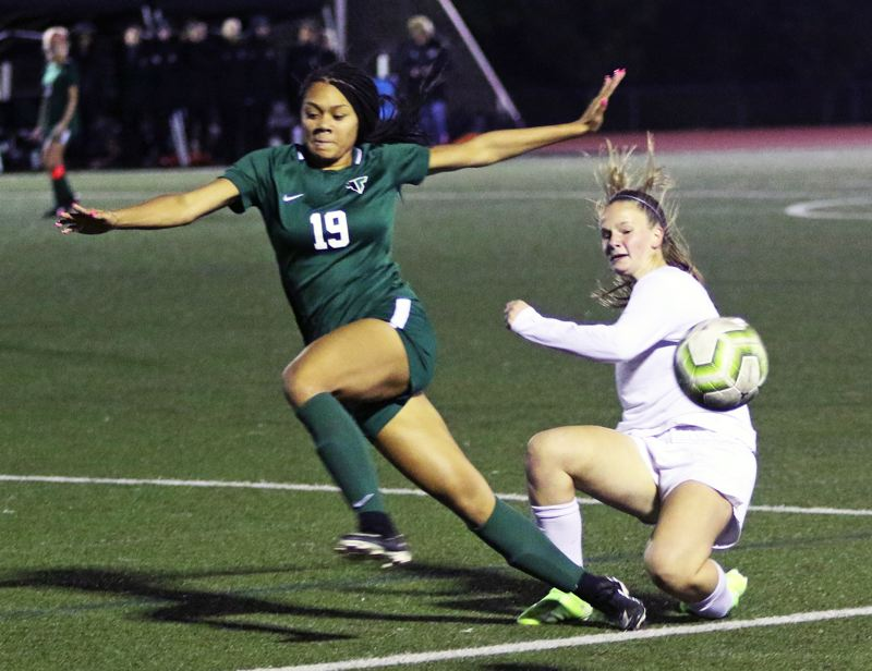 PMG PHOTO: DAN BROOD - Tigard High School junior Ajae Holdman (19) scrambles for a loose ball during the Tigers' match with Tualatin on Tuesday.