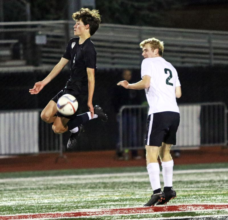 PMG PHOTO: DAN BROOD - Tualatin High School junior Drew Carlile (left) goes up to try and control the ball in front of Tigard junior Jack Hallam during Tuesday's match.