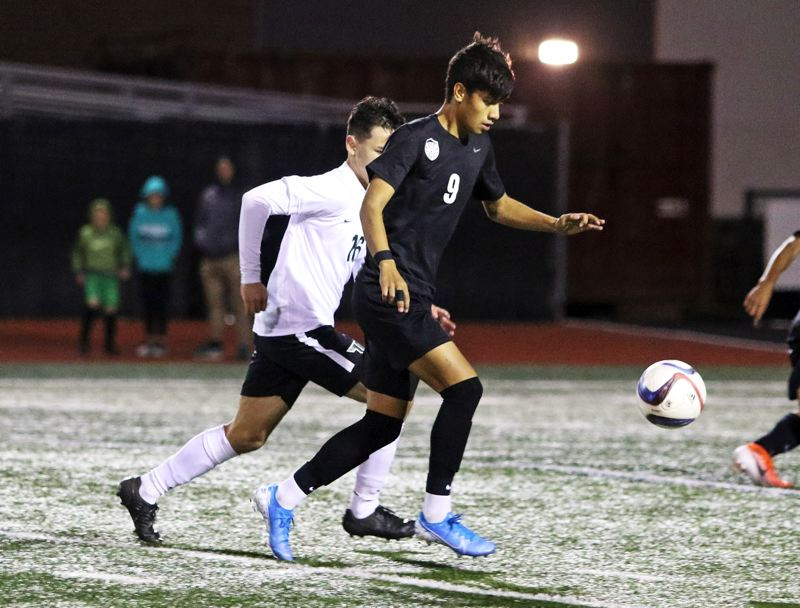 PMG PHOTO: DAN BROOD - Tualatin High School junoir Emmanuel Mayares (9) gets the ball up field during the Wolves' 2-1 win over Tigard on Tuesday.