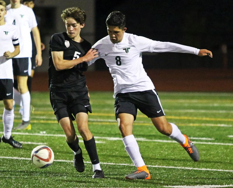 PMG PHOTO: DAN BROOD - Tualatin High School junior Drew Carlile (left) and Tigard senior Ivan Orozco battle for the ball during the teams' Three Rivers League match on Tuesday.