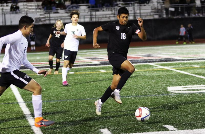 PMG PHOTO: DAN BROOD - Tualatin High School senior Jose Jacintos (18) looks to run down the ball during the Wolves' 2-1 win over Tigard on Tuesday.