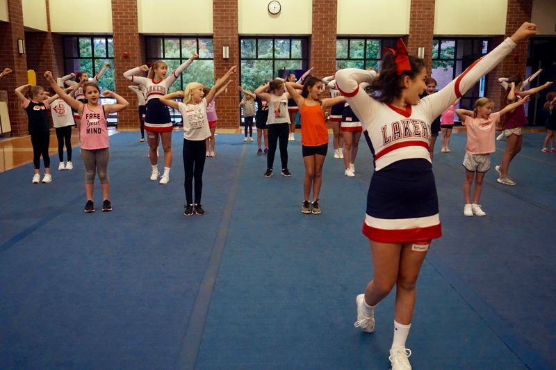 PMG PHOTO: CLAIRE HOLLEY - Laker cheerleader Briana Gutierrez teaches campers arm motions to go along with a cheer.