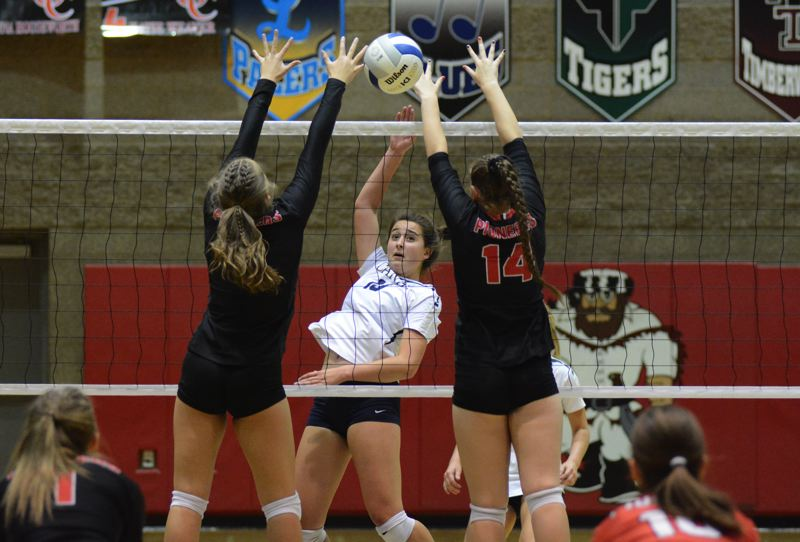 PMG PHOTO: DEREK WILEY - Canby senior Natalie Doman hits the ball past two Oregon City blockers.
