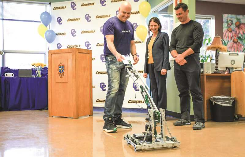 PHOTO COURTESY OF OLIVE AND BLU PHOTOGRAPHY - Facebook Community Development Regional Manager William Marks accepts a note from a VEX Robot Thursday morning containing the announcement of a $200,000 Facebook grant. Looking on are Crook County School District Superintendent Dr. Sara Johnson and Facebook Data Center Site Manager Andrew Gold.