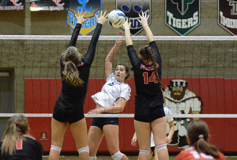 PMG PHOTO: DEREK WILEY - Canby senior Natalie Doman hits the ball past two Oregon City blockers Tuesday.