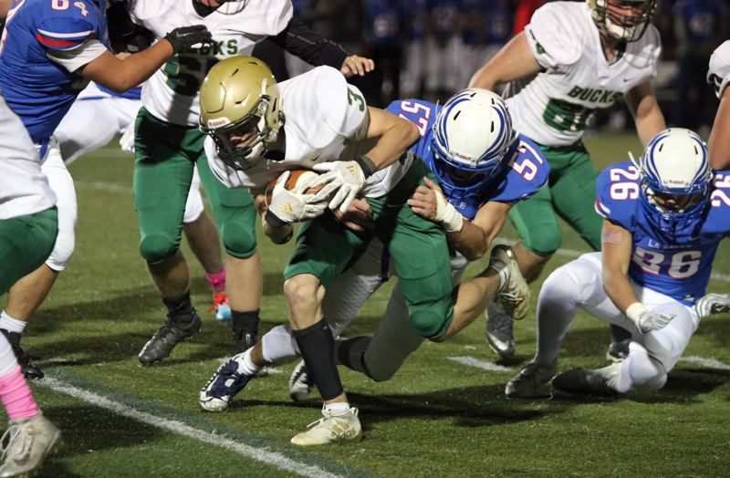 PMG PHOTO: JIM BESEDA - Pendleton running back Zaanan Bane (3) takes La Salle Prep defensive end Michael Drenner (57) for a short ride during the first half of Thursday's 5A Special District 1-East game in Milwaukie.